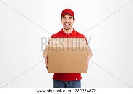 Image of a excited happy young delivery man in red cap standing with parcel post box isolated over white background. Looking camera.