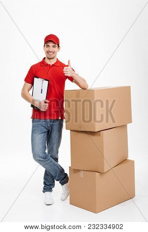 Image of a handsome cheerful young delivery man in red cap standing with parcel post boxes isolated over white background. Looking camera with thumbs up.