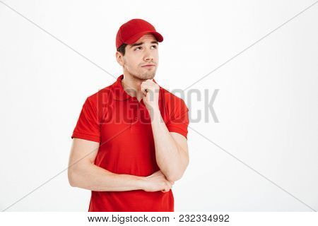 Image of a thinking young delivery man in red cap standing isolated over white background. Looking aside.