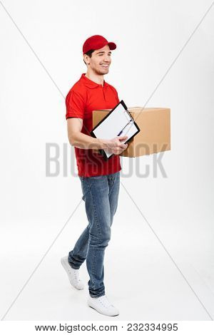 Image of a handsome young delivery man in red cap standing with parcel post box isolated over white background. Looking aside.
