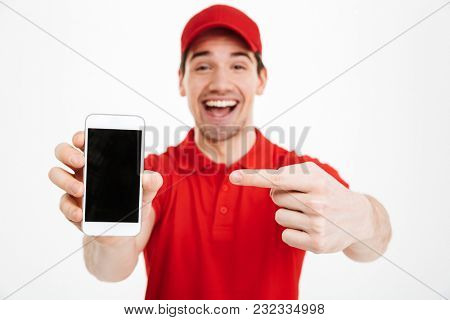 Portrait of a excited happy young delivery man in red cap standing isolated over white background. Looking camera showing display of mobile phone.
