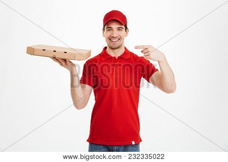 Image of a smiling young delivery man in red cap standing pointing isolated over white background. Looking camera holding pizza.