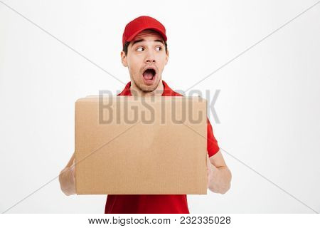 Image of a young shocked excited delivery man in red cap standing with parcel post box isolated over white background. Looking aside.