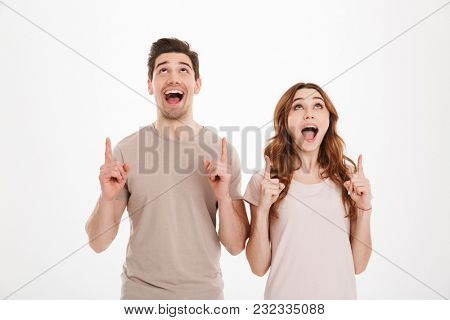 Photo of joyous people 20s man and woman having european appearance wearing beige t-shirts smiling and pointing fingers up on copyspace over white background