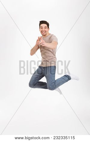 Full-length photo of handsome man 30s in casual t-shirt and jeans jumping and pointing index fingers on camera like hey you isolated over white background
