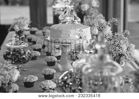 Wedding Party Display Of Cake, Cupcakes, Jars Of Candies, And Bouquets Of Flowers
