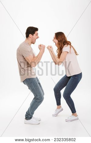 Full length photo of attractive active couple guy and girl wearing beige t-shirts expressing delight standing face to face and clenching fists over white background