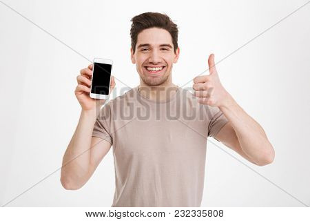 Photo of brunette guy in beige t-shirt holding cell phone with copyspace black screen and gesturing thumb up isolated over white wall