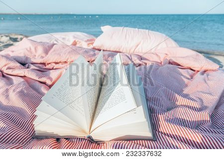 Relax concept. Cozy and comfortable bed near the sea. Summer vacations still life. The text in the book is transformed and not recognizable.