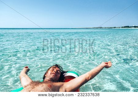Man on lilo in the sea water. Human relaxing on inflatable ring on the beach. Summer vacations.
