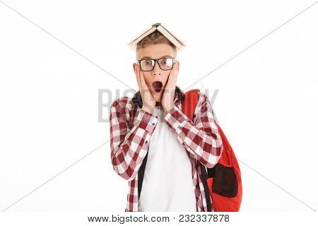 Portrait of a shocked schoolboy in eyeglasses with backpack holding book on his head isolated over white background