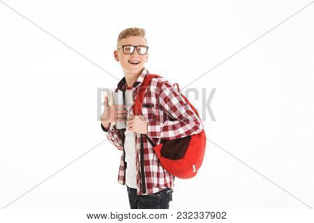 Portrait of a happy schoolboy in eyeglasses with backpack holding books and looking away isolated over white background