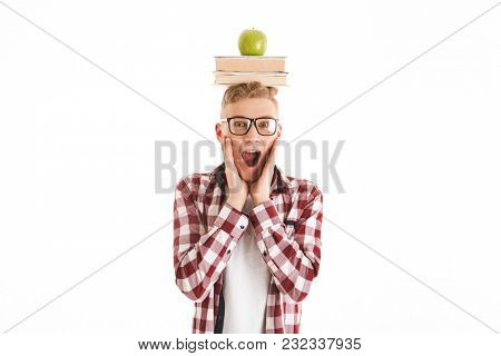 Portrait of an excited schoolboy in eyeglasses holding stack of books and green apple on his head and screaming isolated over white background