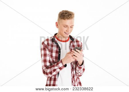 Caucasian teenager in casual t-shirt 17y wearing braces holding cell phone and looking at screen while browsing or typing isolated over white background