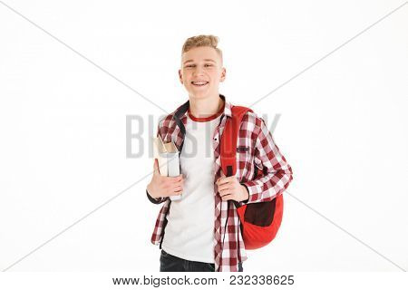 Portrait of a happy schoolboy with backpack holding books and looking at camera isolated over white background
