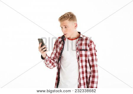 Caucasian teenager in casual t-shirt 17y wearing braces holding smartphone and looking at screen with shock or fear isolated over white background
