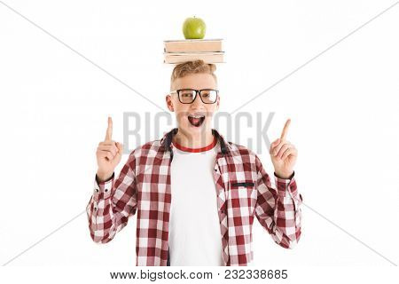 Portrait of a happy schoolboy in eyeglasses holding stack of books and green apple on his head and pointing fingers away at copy space isolated over white background