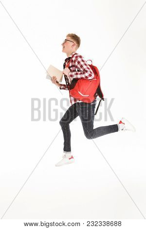 Full length portrait of a smiling schoolboy in eyeglasses with backpack holding books and jumping isolated over white background