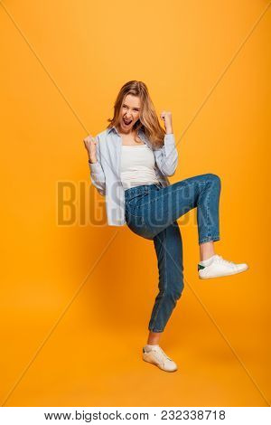 Full length picture of pleased pretty woman yelling and clenching fists, acting like winner or lucky person isolated over yellow background