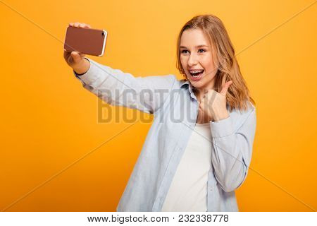 Portrait of a joyful young girl with braces taking a selfie with mobile phone isolated over yellow background