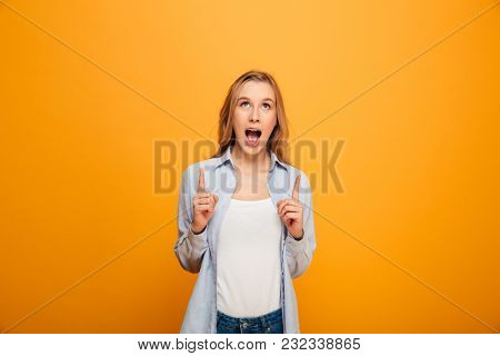 Portrait of pleased pretty woman looking upward and pointing index fingers on copyspace isolated over yellow background