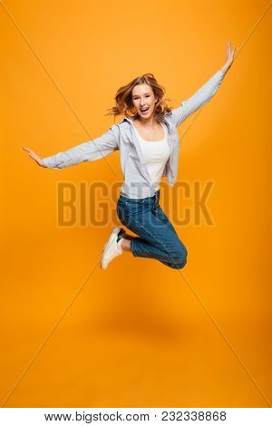 Full length portrait of gorgeous woman expressing happiness and fun while jumping or levitating with hands throwing up isolated over yellow background