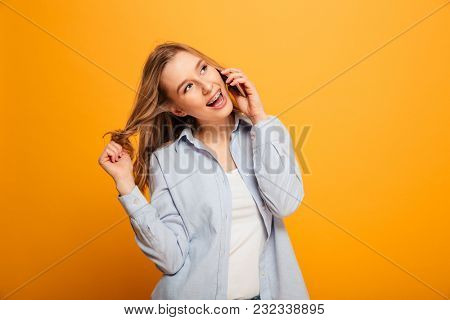 Portrait of a smiling young girl with braces talking on mobile phone isolated over yellow background