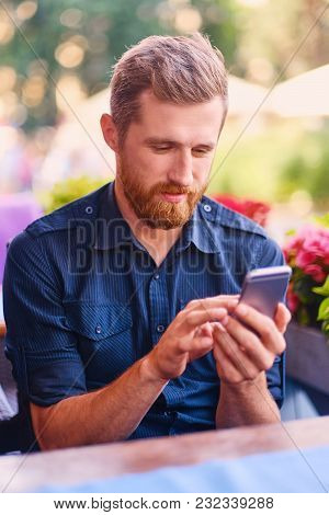 Outdoor Shot Of Handsome Bearded Male Dressed In Casual Clothing With A Phone In A Cafe.