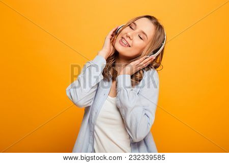 Picture of cute caucasian woman 20s wearing braces in casual clothing listening to music using wireless earphones isolated over yellow background