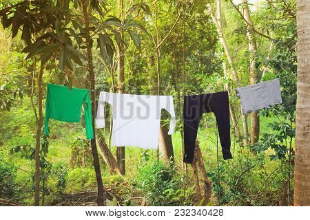 Hanging Out The Clothes On The Rope In The Tropical Yard, White T-short With Copy Space  Hanging In