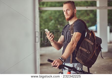 Handsome Redhead Male With A Stylish Haircut And Beard Dressed In Sportswear With A Bicycle And Back