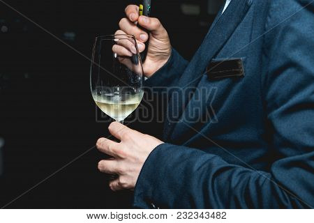 Man In A Blue Suit Holds Glass Of Wine. People Consider The Color Of The Wine And Try How It Smells