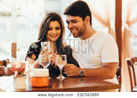Couple At Restaurant Looking At His Smart Phone