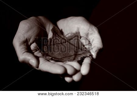 closeup of a ragged Jewish badge in the hands of a man, with a dramatic effect
