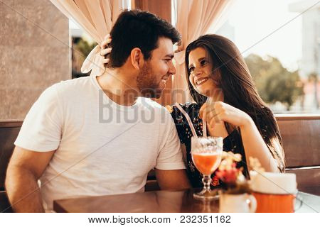 Young Couple In Love Sitting In A Restaurant, Drinking Colorful Drink, Having A Conversation And Enj