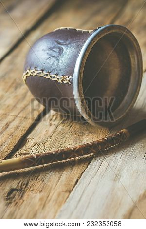 Hand Crafted Artisanal Yerba Mate Tea Leather Calabash Gourd With Straw On Weathered Plank Wood Back