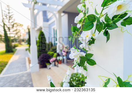 An Artificial Ivy With White Flowers Around The Pillar With Homefront Background.
