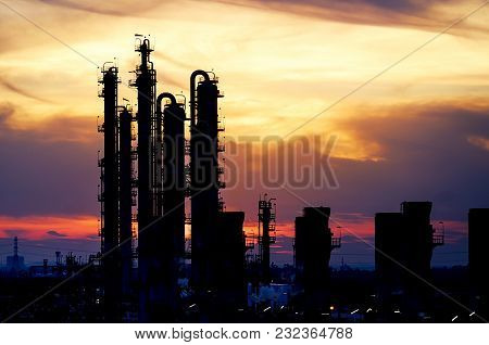 Silhouette Of Distillation Tower In Petrochemical Plant With Sunset Sky Background