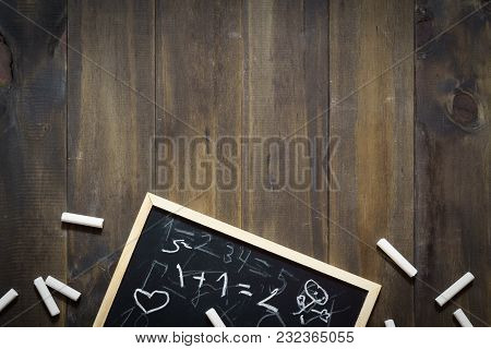 Blackboard And Chalk With Mathematics Written By Children. Back To School Concept On Wooden Backgrou