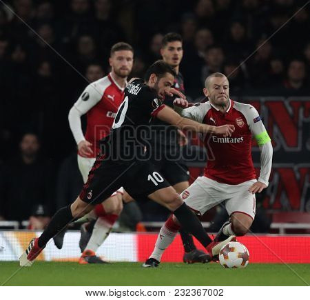 Hakan ??alhanoglu of AC Milan and Jack Wilshere of Arsenal compete for the ball during the Europa League match between Arsenal and AC Milan at The Emirates Stadium on March 15, 2018 in London,
