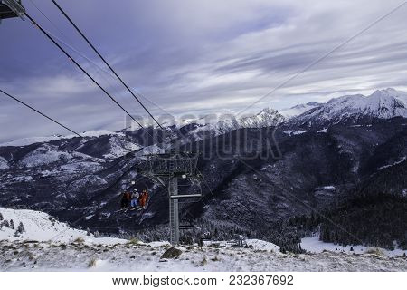 Three Skiers Climbs The Mountains On A Cable Car For Descent.ski Station In The Mountains. There Is