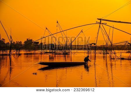 Silhouette Fisherman On Boat Fishing By Using Traditional Net Fishing Tools In Swamp During Sunset