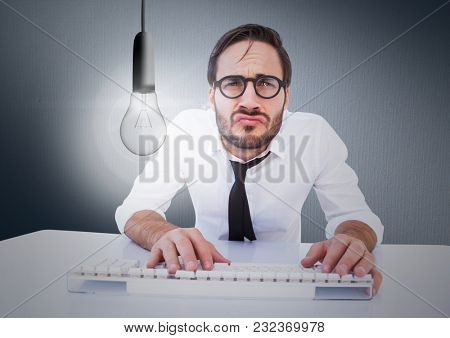 Digital composite of Business at desk with glowing light bulb against navy background