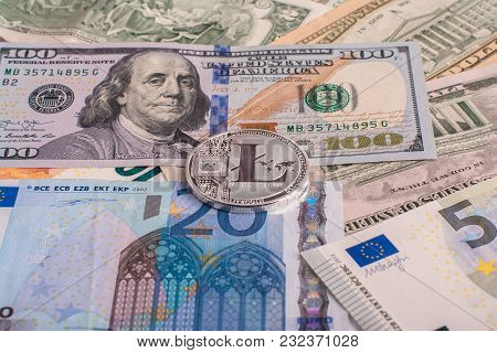 Cryptocurrency Coin Litycoin Lying On The Euro And Dollar Banknotes. Concept Crypto Currency Electro