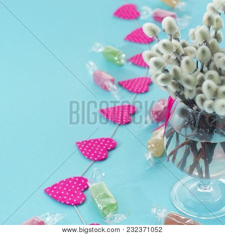 Festive Arrangement In A Glass Vase With Twigs Catkins. Bright Candy Garlands On A Blue Background.