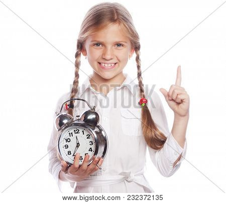 Little girl is holding clock while pointing up with her index finger, isolated over white background