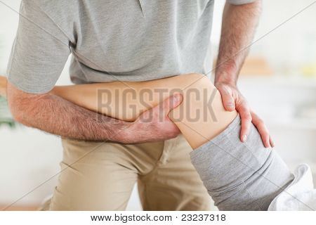 Chiropractor massaging a woman's knee in a room