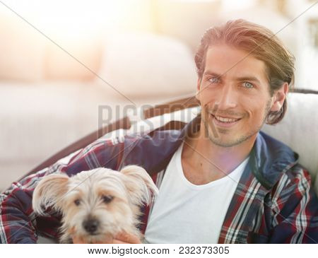 close-up of a smiling guy stroking his dog while sitting in a large armchair.