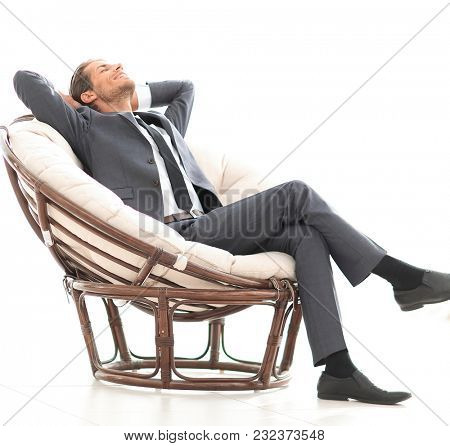 happy businessman relaxing in big comfortable armchair