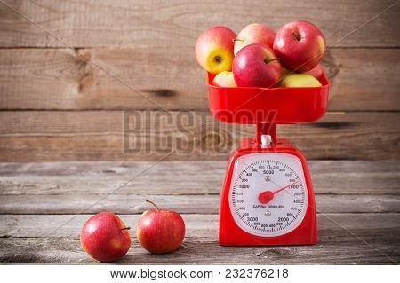 The Red Apples On Red Scales On Wooden Background